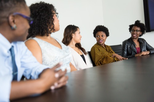 diverse men and women talking in conference room.